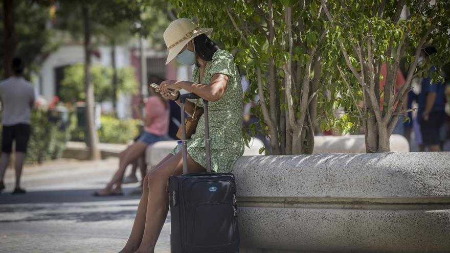 Una mujer con maleta en el entorno de la Catedral. En Sevilla (Andalucía, España), a 27 de agosto de 2020.