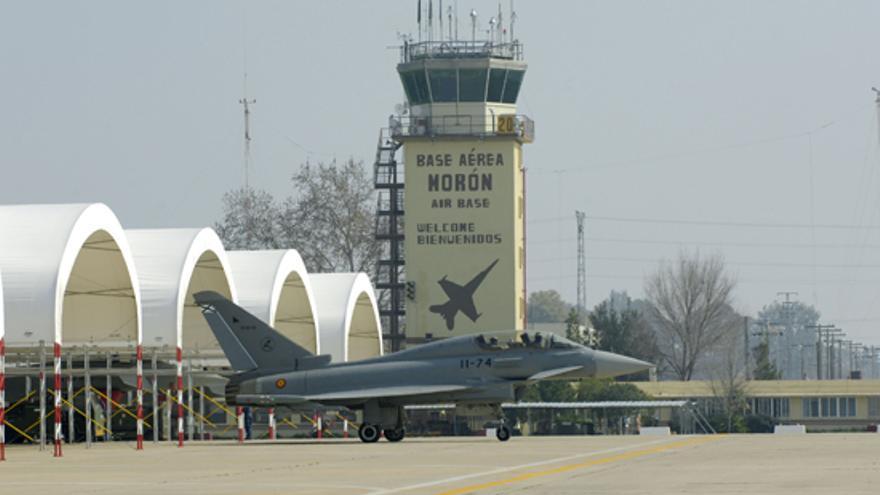 Un avión, a punto de despegar, con la torre de control de la base al fondo.