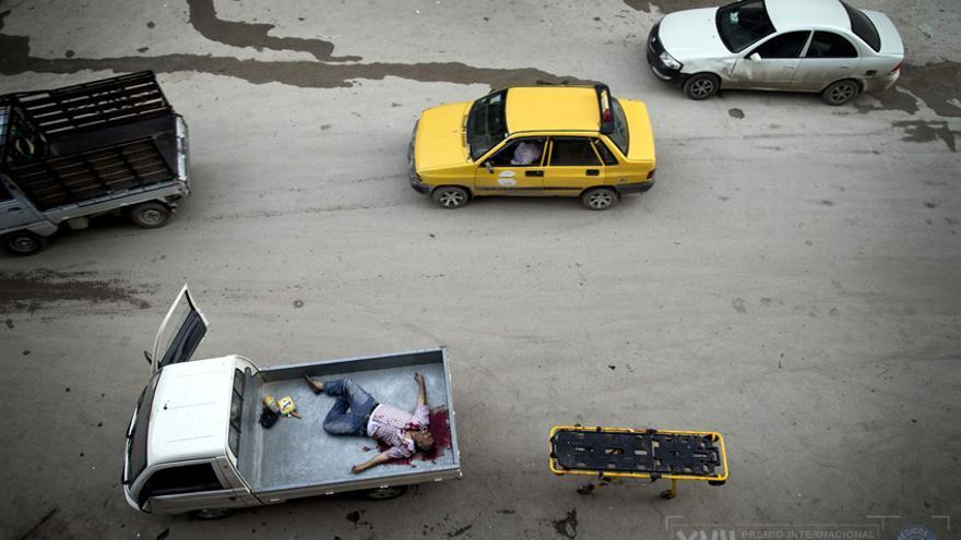 Un civil muerto fuera del hospital Dar al-Shifa en Alepo es llevado en una camioneta con su familia. Fue alcanzado por un francotirador./ Niclas Hammarström