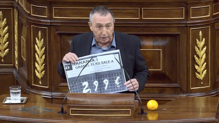 El diputado de Compromís Joan Baldoví, con una naranja, muestra un cartel con el precio de los cítricos