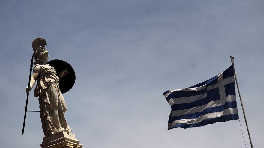 Una bandera griega ondea al lado de la estatua de la diosa Palas Atenea en Atenas.