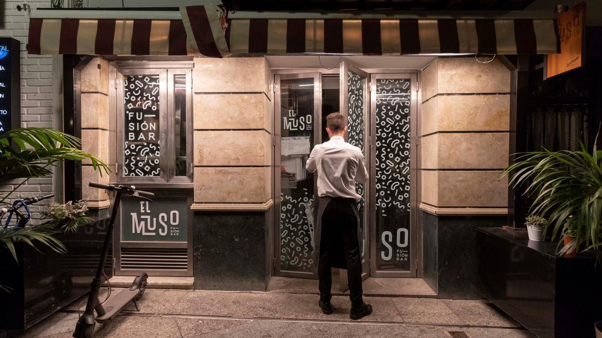 Un camarero cierra la puerta de un bar de la Plaza de Las Flores de Murcia.