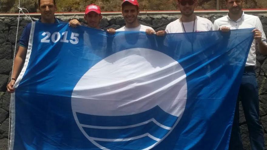En la imagen, el alcalde de Breña Alta (izquierda) y el concejal de Turismo (derecha), con los tres socorristas de la empresa concesionaría del servicio de vigilancia de la playa de Bajamar momentos antes de izar la Bandera Azul.