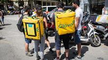 Imagen de varios repartidores con mochilas de Glovo y Deliveroo en Barcelona.