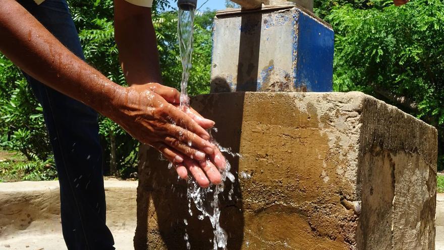 Una persona se lava las manos en uno de los grifos puestos en marcha en las comunidades.