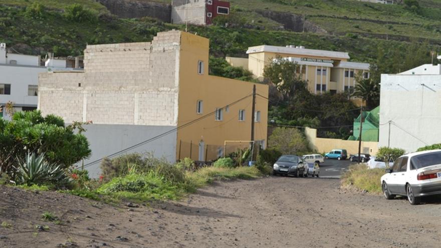 Calle sin asfaltar en Salto del Negro con el colegio que cerró. FOTO: Iago Otero paz