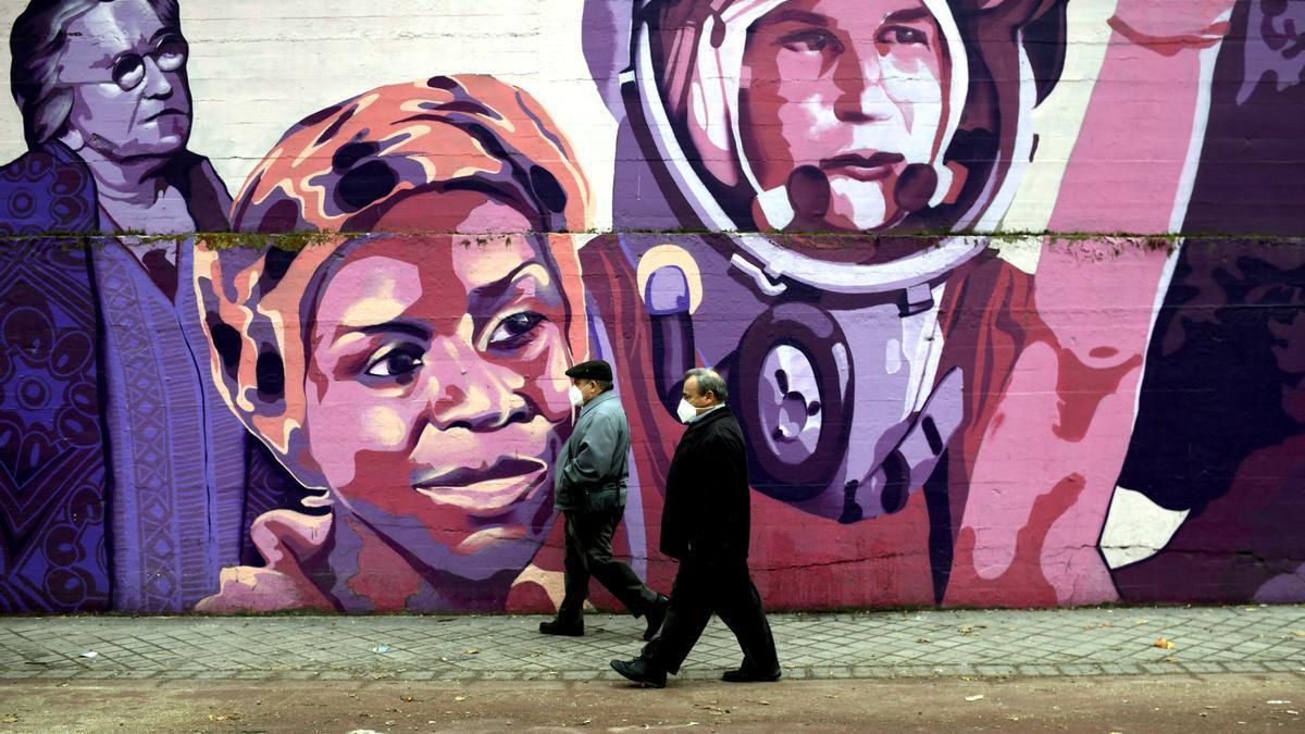 Dos personas pasan por el mural feminista en el polideportivo municipal de la Concepción en el distrito de Ciudad Lineal.