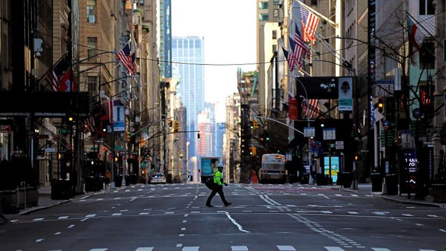 A pedestrian crosses a trafficless Fifth Avenue in New York, New York, USA, 02 April 2020.