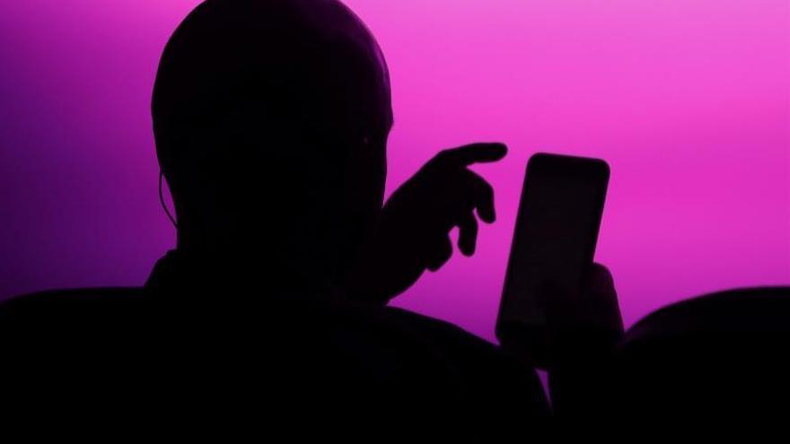 Un hombre consulta su teléfono móvil.