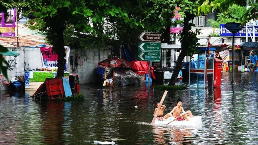 Niños remando en una calle inundada en una ciudad de Tailandia.