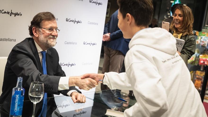 Mariano Rajoy saluda a un joven durante la firma de su libro.