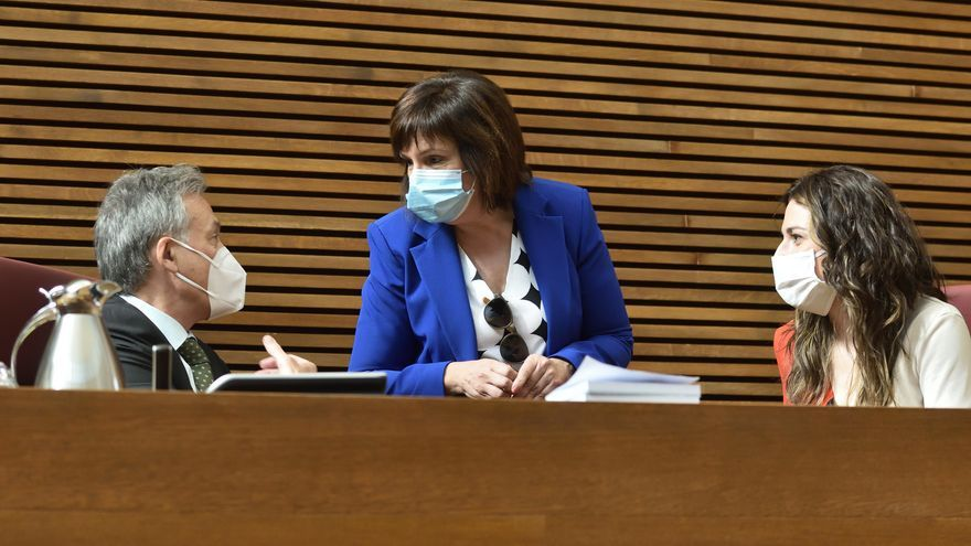 La presidenta de la comisión de reconstrucción, Carmen Martínez (PSPV) dialoga con Aitana Mas (Compromís) y el letrado.