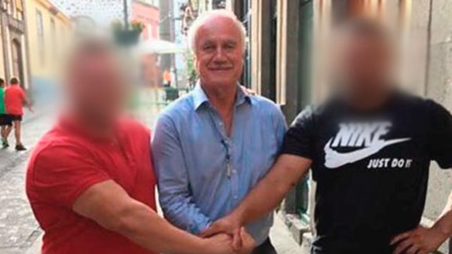 El alcalde de Firgas, Manuel Báez, en una foto con otras dos personas en la que presenta su aspecto actual, con el pelo y el bigote canos.