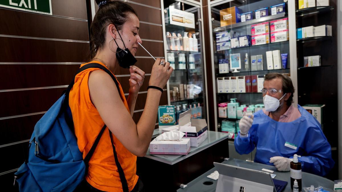 Una joven se practica una prueba COVID en una farmacia de Barcelona