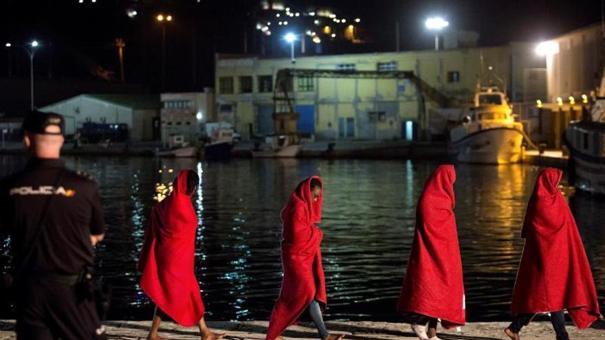 Varios migrantes de origen subsahariano recién llegados a las costas españolas se cubren con las mantas proporcionadas por Cruz Roja.