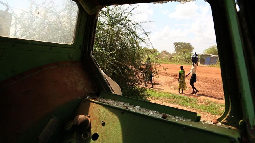 Mujeres sursudaneses caminan por el campo de desplazados tras un tanque con los cristales rotos/ Foto: R. H.