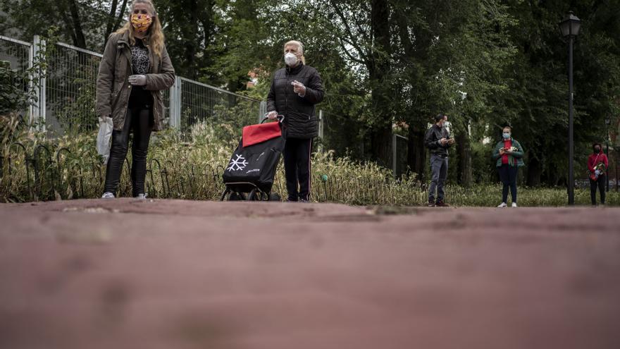 Personas haciendo cola a la espera de recibir alimentos en el punto de recogida.