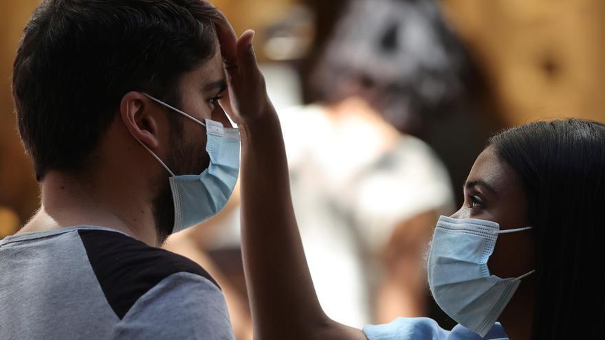 Una pareja con mascarillas en Madrid este sábado durante la ola de calor. EFE/ Mariscal