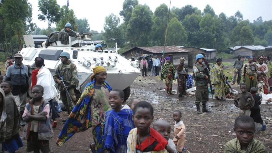 Foto de archivo tomada el 8 de agosto de 2012 de varios refugiados desplazados por los enfrentamientos entre el Gobierno y el grupo rebelde M23 pasan junto a miembros de las tropas de pacificación de la ONU.