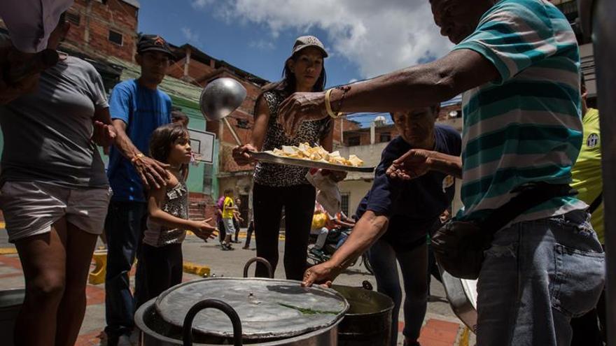 Vecinos de un barrio venezolano se organizan para compartir un plato de sopa