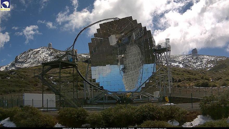 En la imagen, tras uno de los telescopios MAGIC,  este viernes, las zonas altas del Observatorio del Roque  con nieve.