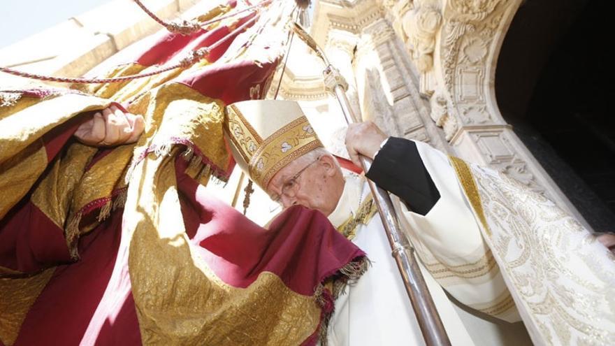 Antonio Cañizares besa la Reial Senyera a su entrada a la catedral en 2014.