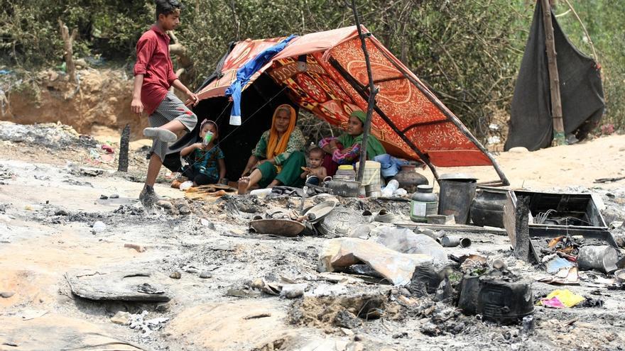 rohinyás se resguardan del calor en una tienda improvisada frente a los escombros de viviendas devastadas por el fuego, en una barriada de Jammu (India).