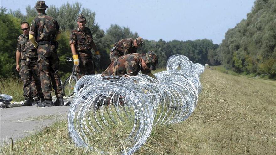 Militares húngaros colocan alambre de espino en la frontera de Hungría con Serbia y Croacia en 2015.