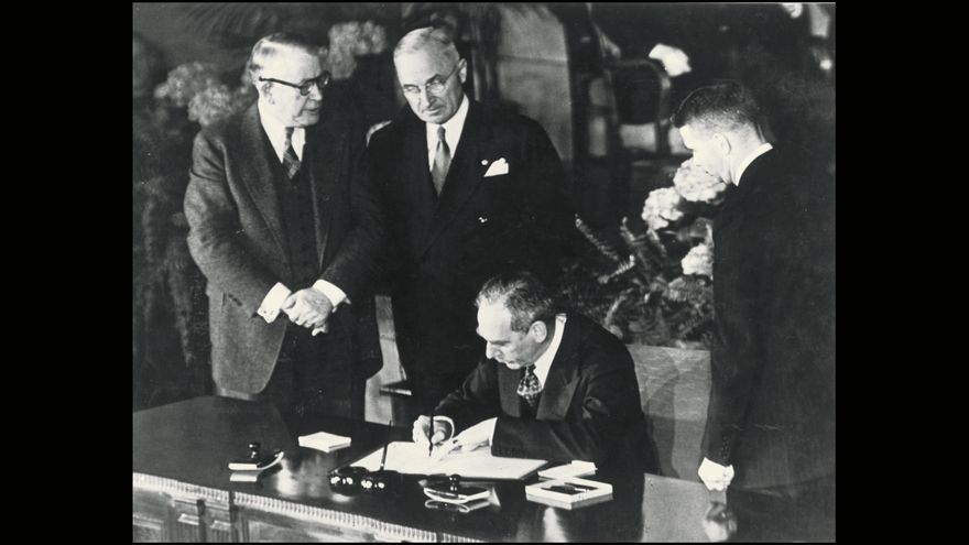 Secretary of State Dean Acheson signs the Atlantic defense treaty for the United States, April 4, 1949. Vice President Alben W. Barkley, left, and President Harry Truman converse during the signing.