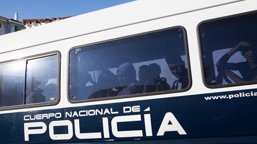 Jóvenes de origen magrebí son trasladados en una furgoneta de la Policía de Fronteras desde el polideportivo Andrés Mateo de Algeciras.
