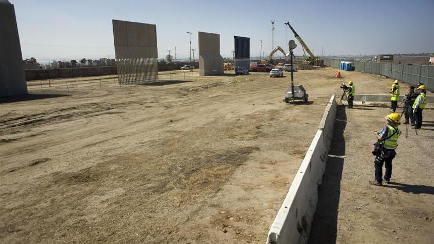 Avanza la construcción de los prototipos del muro según lo estimado por el Gobierno Unos periodistas (d) observando las labores de construcción de los prototipos del muro fonterizo en un lote a unas tres millas al este de la garita internacional de Otay Mesa, en San Diego, California.