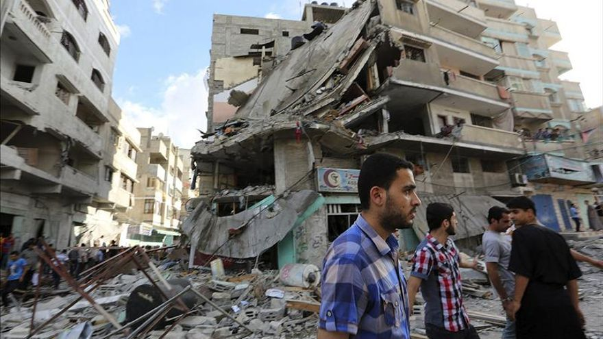 Imagen de archivo. Unos hombres observan los daños materiales en un edificio destruído durante un atáque aéreo del ejército israelí en la franja de Gaza, el 18 de julio de 2014.