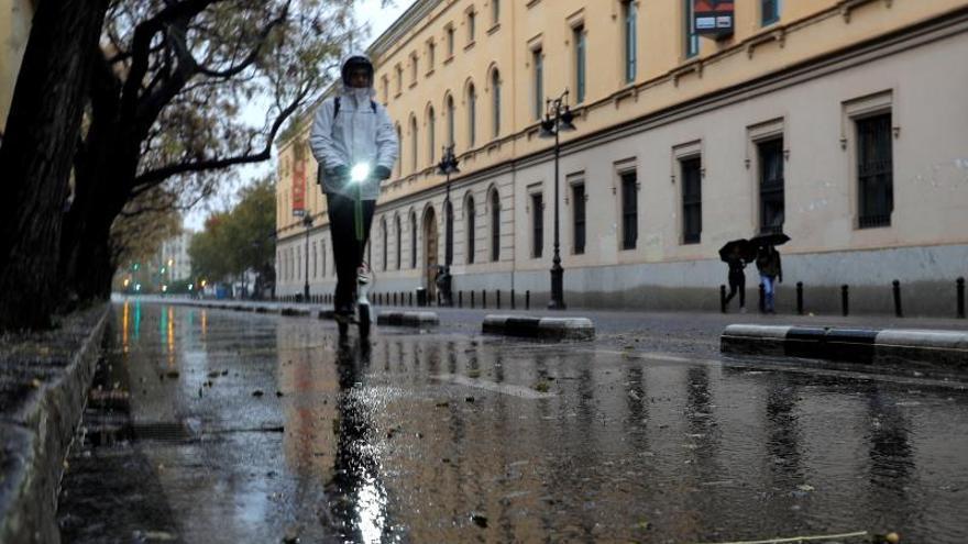 Una persona circula bajo la lluvia en un patinete eléctrico en Valencia.