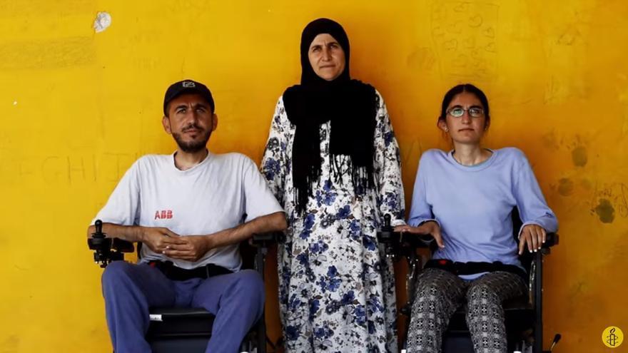 Alan Mohammad and his sister Gyan (ambos con distrofia muscular) posan junto a su madre en el campo de refugiados de Ristona, en Grecia | FOTO: Amnistía Interncional