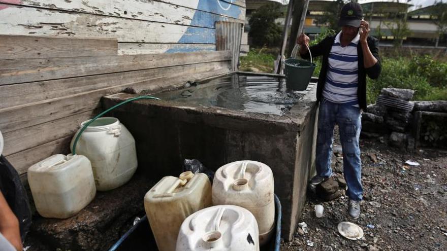 """Un hombre llena botes de agua para su consumo este martes, en Tegucigalpa (Honduras). Más de 900.000 personas están en situación de inseguridad alimentaria por la sequía que afecta a gran parte de Honduras, especialmente el llamado Corredor Seco, una cifra que puede aumentar hasta más de un millón durante los próximos meses. Un estudio elaborado en 2019 por la Unidad Técnica de Seguridad Alimentaria y Nutricional de Honduras (UTSAN), al que tuvo acceso Efe, revela que """"1 de cada 5 hogares en el Corredor Seco ha experimentado hambre""""."""