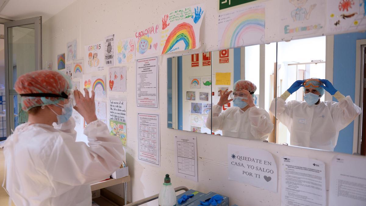 Dos sanitarios se colocan los EPIS momentos antes de entrar en la zona de Urgencias, del Hospital Pío del Rio Hortega de Valladolid