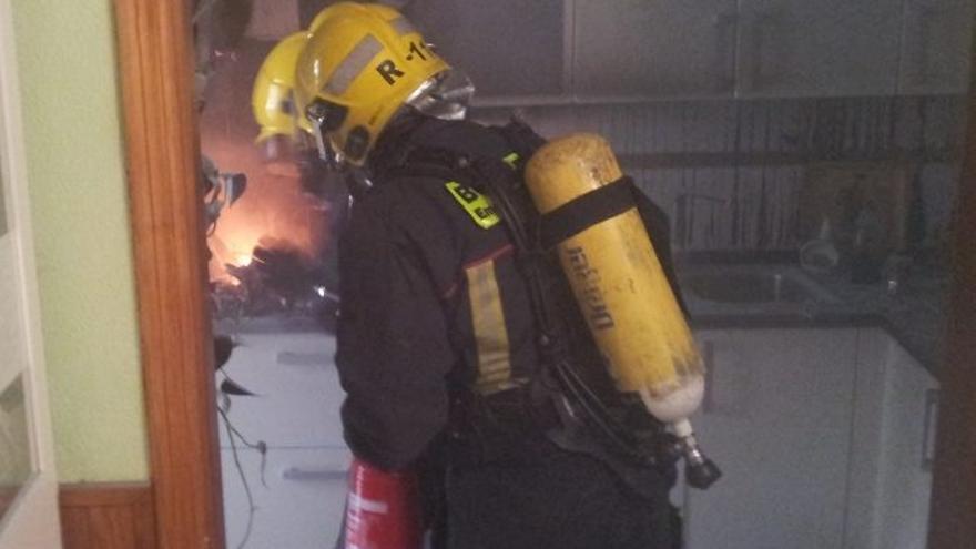En la imagen, dos bomberos durante las tareas de extinción del fuego registrado en la cocina de una vivienda de la capital. Foto: BOMBEROS LA PALMA.
