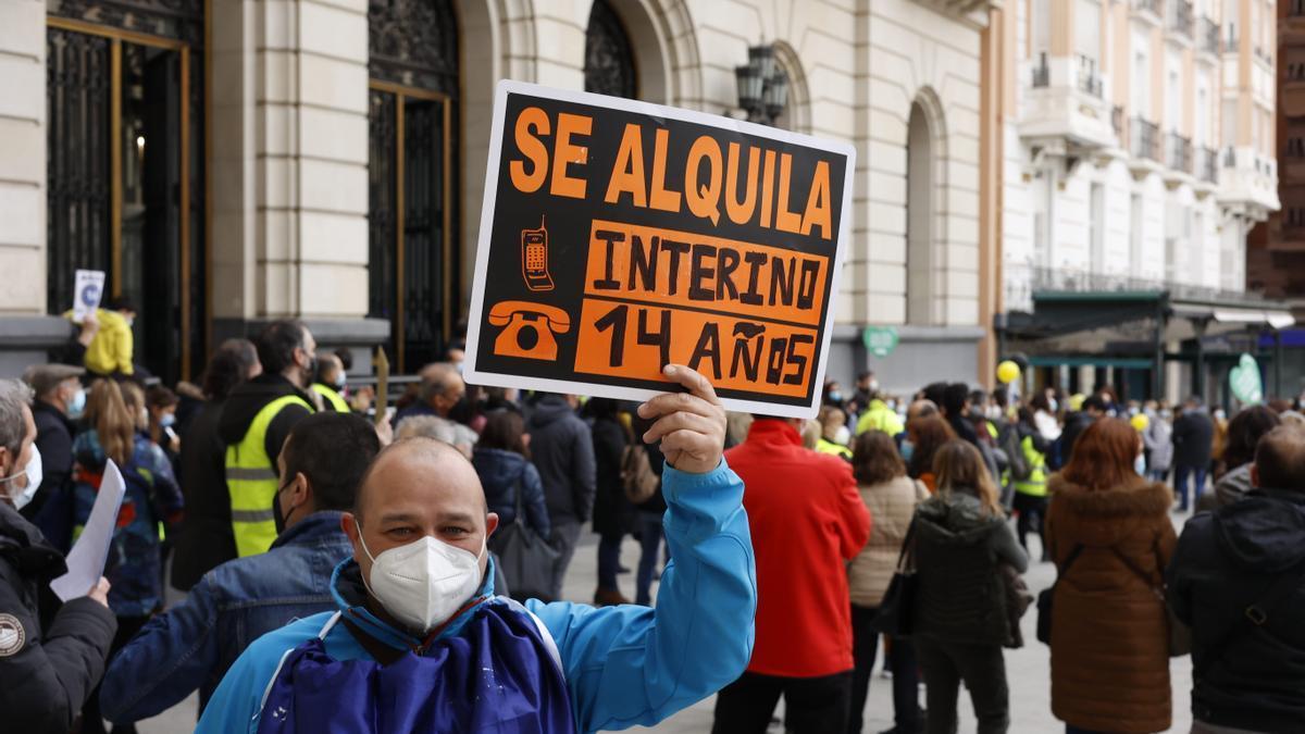"""Un trabajador interino se manifiesta con una pancarta donde se puede leer """"Se alquila, interino 14 años"""" en una imagen de archivo."""