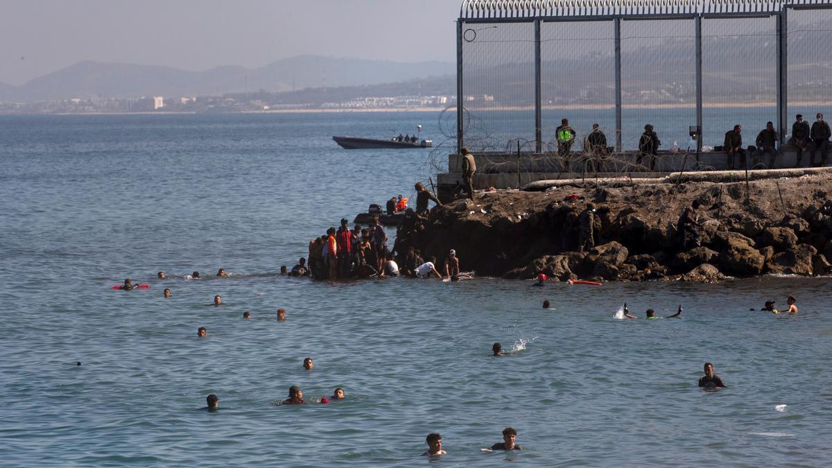 Un grupo de inmigrantes intenta cruzar el espigón junto al paso fronterizo del Tarajal en Ceuta, el 18 de mayo de 2021 en una avalancha de inmigrantes sin precedentes en España. EFE/ Brais Lorenzo/Archivo