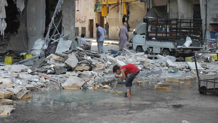 Barrio de Kalaseh en Alepo, una zona atacada por misiles en agosto de 2014. La foto fue tomada el 1 de septiembre y muestra a un niño bebiendo agua del lugar donde ha caído un misil. Amnesty International (Photo: Mujahid Abu al-Joud) .