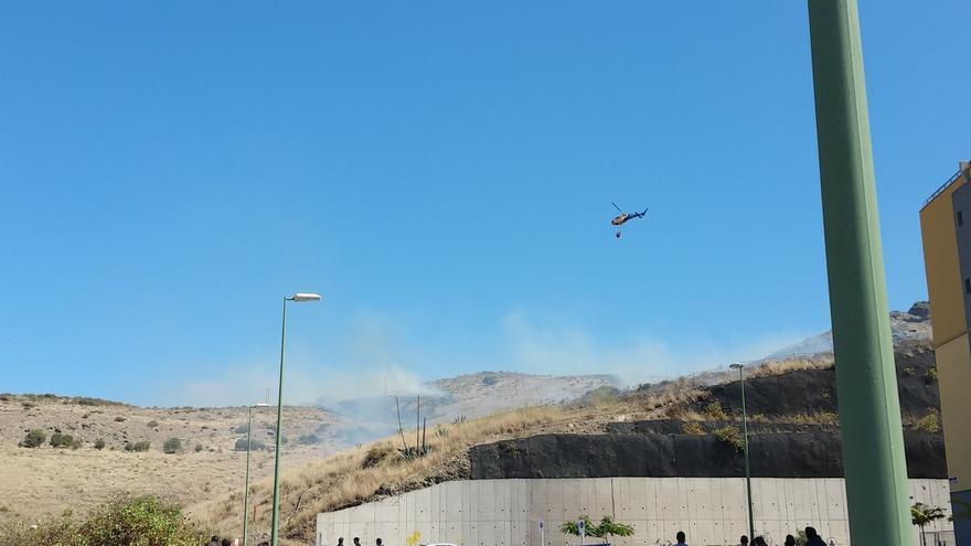 Un helicóptero trata de sofocar el fuego declarado en Ciudad del Campo. (@PoliciaLPA)
