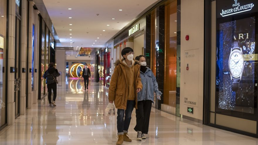 Dos jóvenes chinos con mascarillas pasean por un centro comercial prácticamente vacío en Shangay.