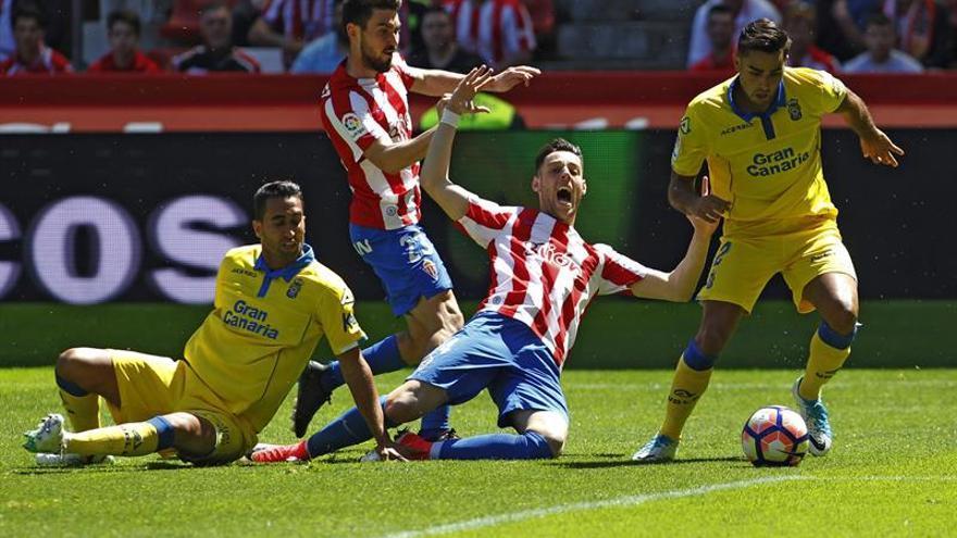 David Simón conduce el balón ante la mirada de Ángel Montoro y dos jugadores del Sporting. (EFE)