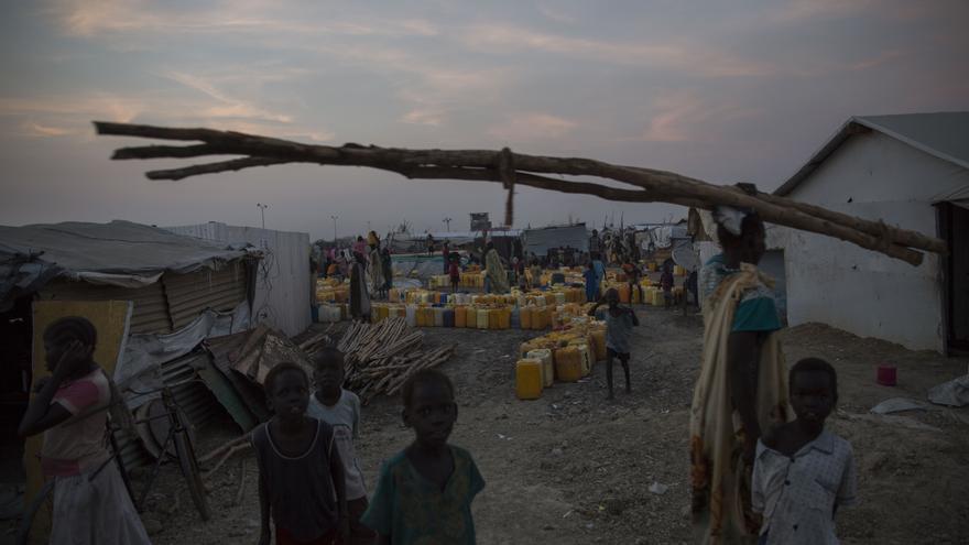 Una larga hilera de bidones señala uno de los escasos puntos de agua del campo. Los grifos están conectados a una cisterna que se llena de agua dos veces al día. En muchas ocasiones, grupos de mujeres tienen que esperar su turno durante horas y no siempre consiguen el agua que necesitan.  La falta de higiene, el hacinamiento y la bajada de las temperaturas hacen que  MSF prevea que la salud de los desplazados empeore a no ser que las condiciones del campo mejoren inmediatamente. Fotografía: Anna Surinyach/MSF