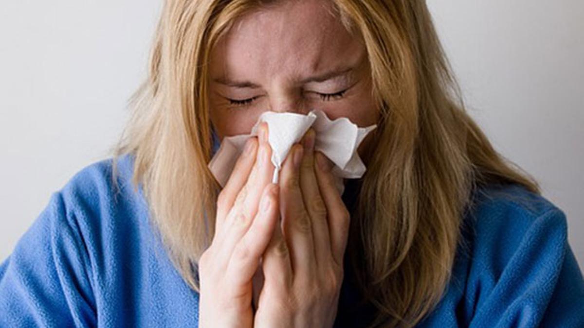 Una mujer estornuda