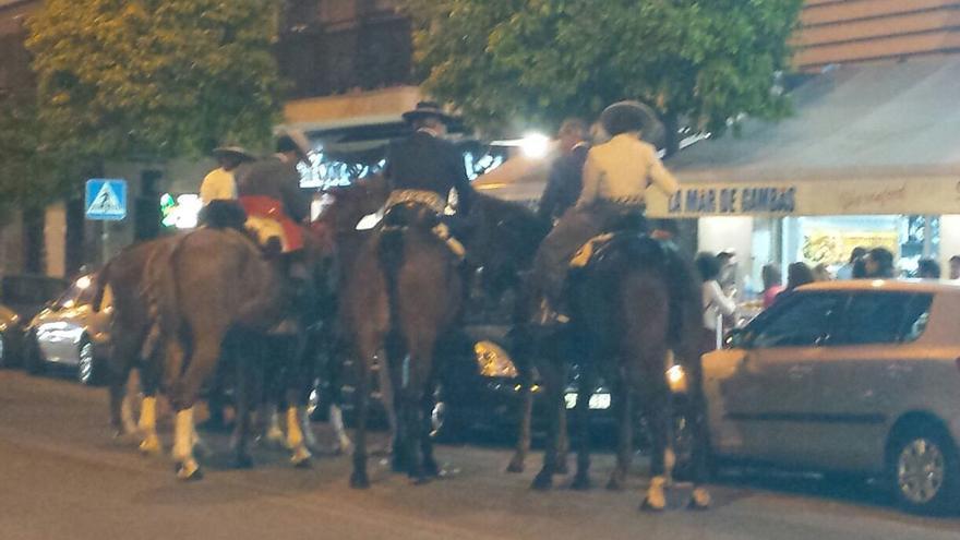 Unos caballistas en un bar de Sevilla tras ser desalojados del Real al terminar el horario de caballos.