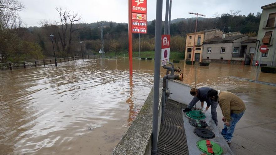 Unas personas realizan su trabajo en el río Ter, que se ha desbordado a su paso por la ciudad de Girona, en el punto más bajo de su recorrido, junto a la carretera C-255.