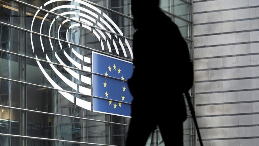 Una persona camina frente a la fachada del Parlamento Europeo en Bruselas.