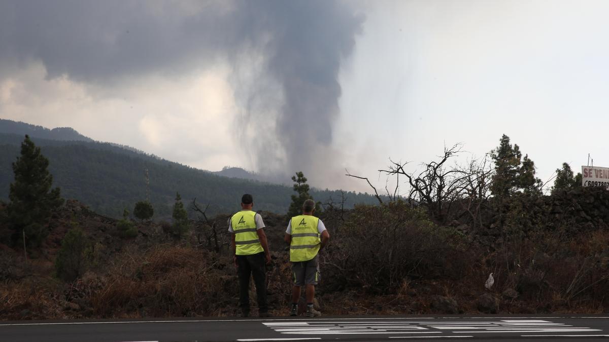 Dos trabajadores de una gasolinera observan la columna de humo y cenizas que emana del volcán de La Palma