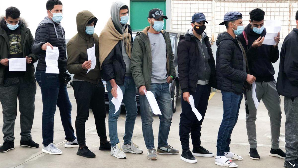Varios migrantes esperan con su solicitud de readmisión a las puertas del Canarias 50